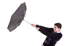 El muchacho joven con un paraguas dio vuelta por el viento Fotos de archivo