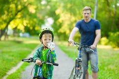 el muchacho joven con una botella de agua está aprendiendo montar una bici con su padre imagen de archivo