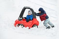 El muchacho joven da un empuje al coche de su Brother pegado en la nieve Foto de archivo