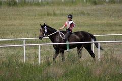 El muchacho joven del Kazakh está montando un caballo breeded puro del Kazakh y se está preparando para competir con Imagen de archivo libre de regalías