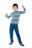 El muchacho joven detiene sus pulgares Imagenes de archivo