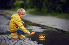 El muchacho joven en botas y capa de lluvia está poniendo los barcos de papel en el agua, en el día lluvioso de la primavera fotografía de archivo