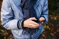 El muchacho joven en chaqueta gris con la bufanda gris sostiene y utiliza smartphone con los auriculares exteriores sobre fondo d fotos de archivo