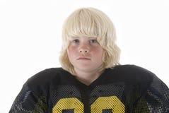 El muchacho joven en doblar uniforme del fútbol americano arma Fotos de archivo libres de regalías