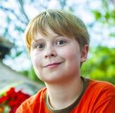 El muchacho joven en la playa está sonriendo Foto de archivo