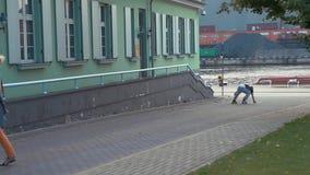El muchacho joven en patinadores del rodillo salta de la cerca en la calle, cayendo Manía extrema almacen de video