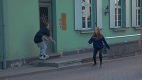 El muchacho joven en rodillos salta en la cerca en la calle El caminar de la gente Manía extrema almacen de video