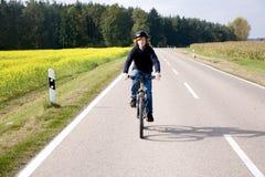 El muchacho joven en su bici de montaña está en un viaje de la bicicleta a lo largo del beauti Foto de archivo libre de regalías