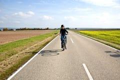 El muchacho joven en su bici de montaña está en un viaje de la bicicleta a lo largo del beauti Imagenes de archivo