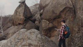 El muchacho joven en un equipo casual elegante y con la mochila turística vaga en las montañas, para y toma un selfie metrajes