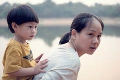 El muchacho joven encendido apoya de su madre: Foucus suave foto de archivo