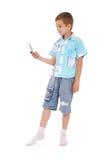 El muchacho joven envía el mensaje de texto con el teléfono Foto de archivo