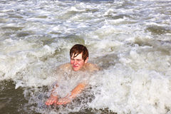 El muchacho joven es cuerpo que practica surf en las ondas Imagen de archivo
