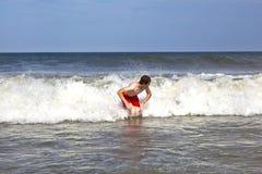 El muchacho joven es cuerpo que practica surf en las ondas Fotografía de archivo libre de regalías
