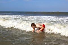 El muchacho joven es cuerpo que practica surf en las ondas Fotos de archivo libres de regalías