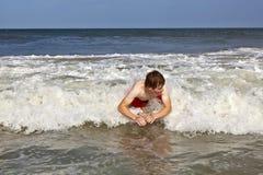 El muchacho joven es cuerpo que practica surf en las ondas Foto de archivo libre de regalías