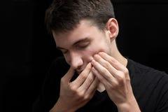 El muchacho joven es sufrimiento del dolor de muelas doloroso Imagen de archivo libre de regalías