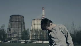 El muchacho joven es toses y puso la máscara de la contaminación contra las chimeneas de la fábrica Concepto de la contaminaci?n  almacen de video
