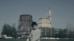 El muchacho joven es toses y puso la máscara de la contaminación contra las chimeneas de la fábrica Concepto de la contaminaci?n  metrajes
