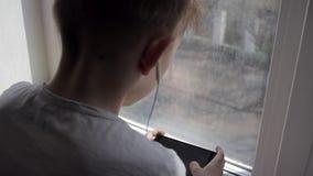 El muchacho joven escucha música en auricular en el teléfono en hogar almacen de video