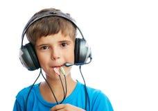 El muchacho joven está escuchando la música Foto de archivo
