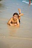 El muchacho joven está mintiendo en la playa Imagen de archivo libre de regalías