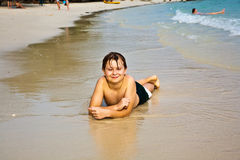 El muchacho joven está mintiendo en la playa Fotografía de archivo libre de regalías