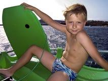 El muchacho joven está practicando surf en el océano Imágenes de archivo libres de regalías