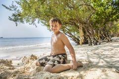El muchacho joven feliz está cavando en la arena de la playa Foto de archivo libre de regalías