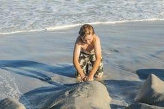 El muchacho joven goza el jugar en la playa arenosa Foto de archivo