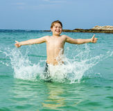 El muchacho joven goza el saltar en el océano Fotografía de archivo