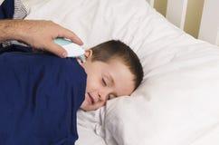 El muchacho joven hace su temperatura tomar con un termómetro digitial fotos de archivo libres de regalías