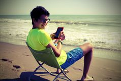 El muchacho joven lee el ebook y pantalones cortos en la playa con efecto del vintage Foto de archivo libre de regalías