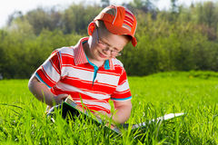 El muchacho joven lee el libro en parque al aire libre Imagenes de archivo