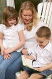 El muchacho joven lee a su madre y hermana Fotografía de archivo libre de regalías