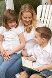 El muchacho joven lee a su madre y hermana Imágenes de archivo libres de regalías