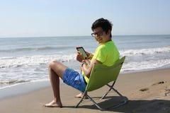 El muchacho joven lee un eBook tecnológico en la playa Fotografía de archivo libre de regalías
