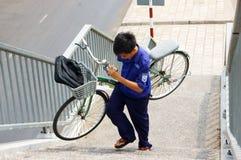 El muchacho joven lleva la bicicleta a mano Fotografía de archivo