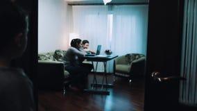 El muchacho joven observa como mujer y hombre que usa el ordenador en sala de estar, habla con el papá almacen de video