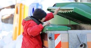 El muchacho joven pobre intenta comer en la caja inútil Imágenes de archivo libres de regalías