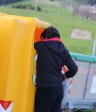 el muchacho joven pobre mira en el cubo de la basura Foto de archivo libre de regalías