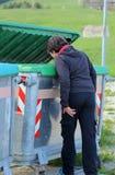 el muchacho joven pobre mira en el cubo de la basura Fotografía de archivo