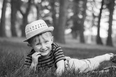 El muchacho joven pone en la hierba en el parque Fotos de archivo libres de regalías