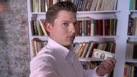 El muchacho joven pone el libro en el estante, dólar del hallazgo, lo puso en el bolsillo, robando concepto metrajes