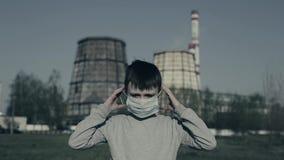 El muchacho joven puso la máscara de la contaminación contra las chimeneas de la fábrica Concepto de la contaminaci?n atmosf?rica metrajes