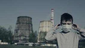 El muchacho joven puso la máscara de la contaminación contra las chimeneas de la fábrica Concepto de la contaminaci?n atmosf?rica almacen de video