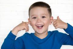 El muchacho joven que lleva la chaqueta azul con el suyo observa la cubierta abierta sus oídos Imágenes de archivo libres de regalías