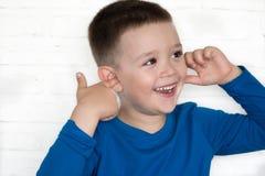 El muchacho joven que lleva la chaqueta azul con el suyo observa la cubierta abierta sus oídos Imagen de archivo