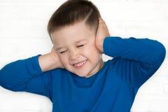 El muchacho joven que lleva la chaqueta azul con el suyo observa la cubierta cerrada sus oídos para oír Imagenes de archivo