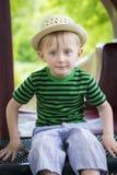 El muchacho joven que lleva un sombrero de ala se sienta en el equipo del patio Fotos de archivo